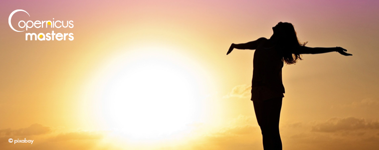 A woman silhouette standing in sunset with arms open wide
